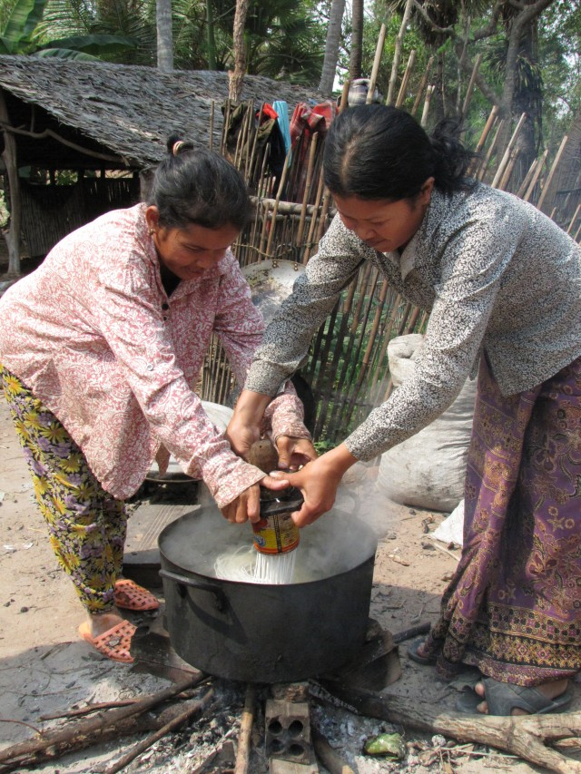 Women in Cambodia making noodles over a fire. Photo: Ana Rojas