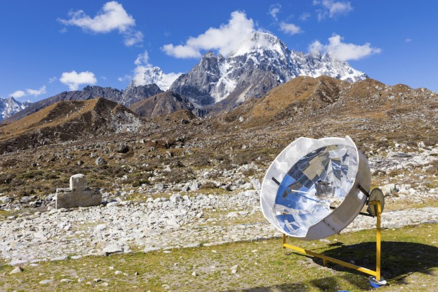 Solar panel cooker heating water kettle, Nepal.