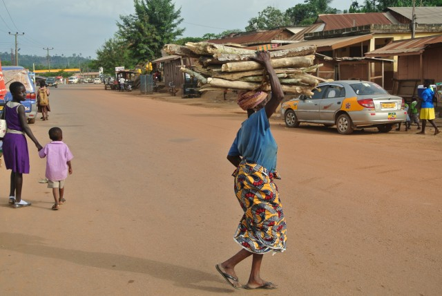 Woman transports fuelwood on her head in Ghana.